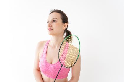 スポーツウェアを着てバドミントンをする外国人の女性