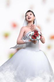 純白のウエディングドレスを着た花嫁が赤い花のブーケトスをしようと上を見上げる