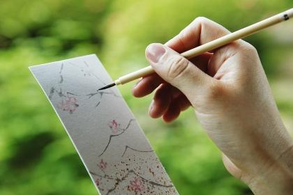 筆で俳句を書く女性