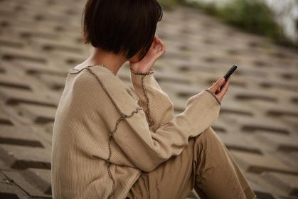スマートフォンを見て落ち込む女性