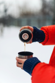Woman in orange jacket  pouring herself a warm cup of hot tea ou
