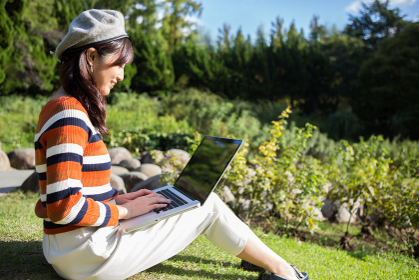 公園でノートパソコンを使う女性