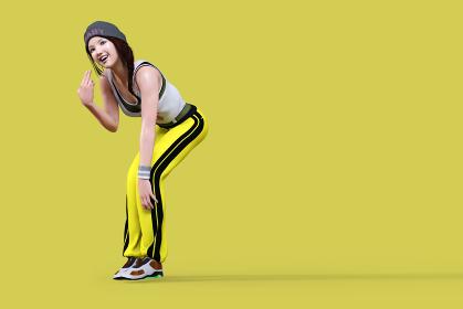 イエローバックにニット帽をかぶり黄色いジャージを履いたスポーテイーな女性が挑戦的なハンドサインをする