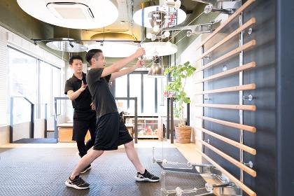 トレーナーに教わりながら広背筋をトレーニングする男性