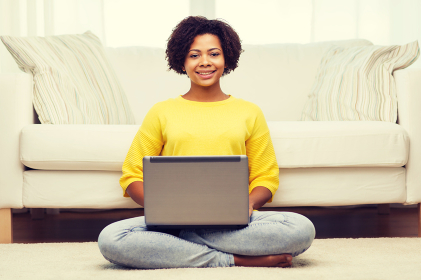 happy african american woman with laptop at home