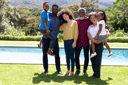 Multi-generation mixed race family enjoying their time at a garden with a pool, standing by the pool, embracing, looking at the camera and smiling