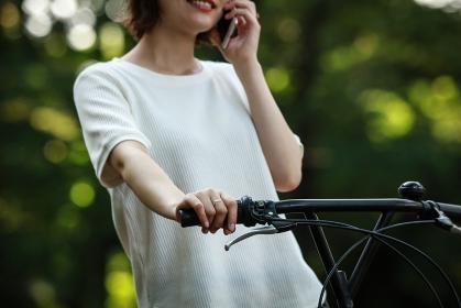 自転車に乗りながら通話する女性
