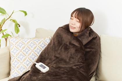 電気毛布で体を温める日本人女性
