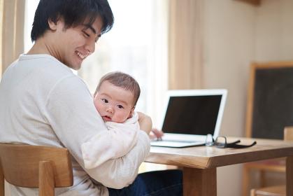 赤ちゃんの子守りをしながら仕事をするアジア人のお父さん