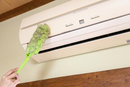 ハンディモップでエアコンの掃除をしている主婦