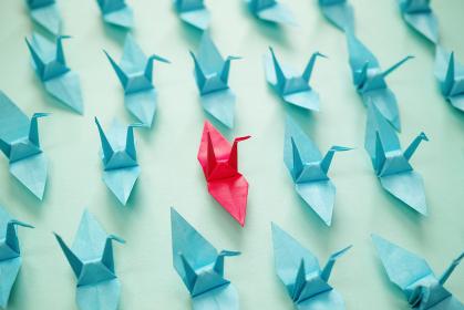 複数の右向きの青い折り鶴の中に一つだけ赤い折り鶴がある。