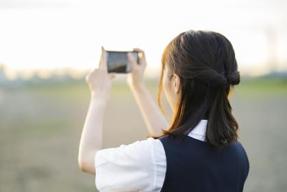 スマートフォンで景色を撮影するアジア人女性の高校生