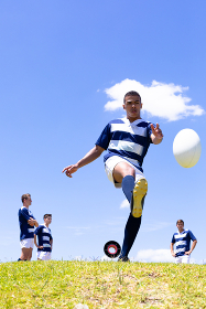 Low angle front view of a mixed race male rugby player kicking a rugby ball, with a group of Caucasian male teammates standing behind him, all wearing a team strip, on a rugby pitch during a match, with blue sky in the background