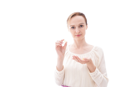 サプリメントを飲む笑顔の若い女性