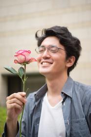 一輪の薔薇を持つ男性