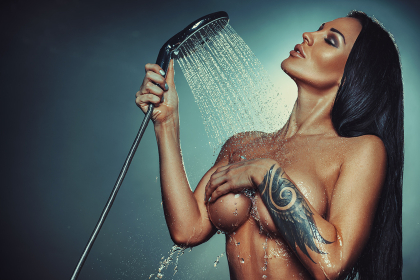 Young sexy nude brunette woman fashion portrait with shower. Tattoo on hand.