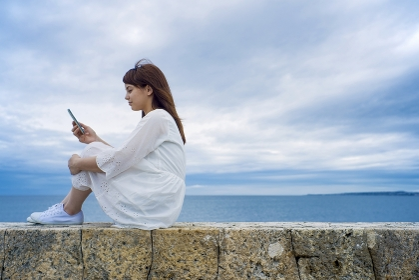 海岸に座ってスマートフォンを見る日本人女性