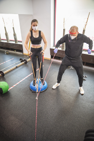 young woman training with his personal trainer indoors