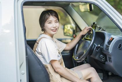 車の運転席に座る若い女性