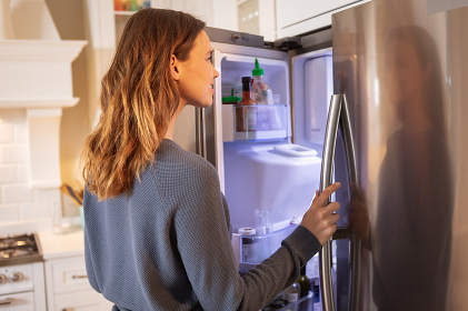 Caucasian woman spending time at home in the kitchen, opening the fridge. Lifestyle at home isolating, social distancing in quarantine lockdown during coronavirus covid 19 pandemic.