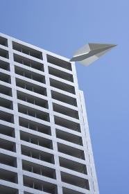 マンションと紙飛行機の合成