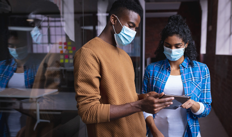 Diverse male and female colleagues at work discussing and looking at tablet wearing face masks. independent creative design business during covid 19 coronavirus pandemic.
