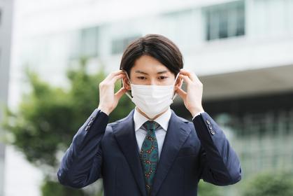 マスクを外す若いビジネスマン・コロナの終わり・明るい未来