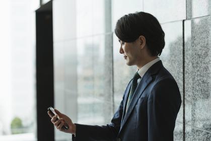 スマートフォンを持つ若い男性・IoTとビジネスのイメージ(逆光・横顔・シルエット)