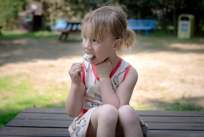 Young girl sitting on table and eating ice cream