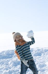 雪原で雪玉を持つ男の子