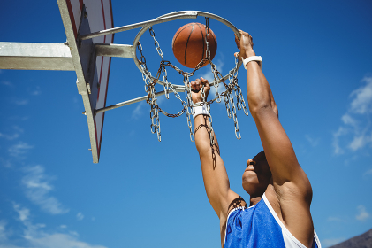 Low angle view of teenager hanging on basketball hoop