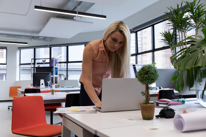 Caucasian woman working in modern office using laptop computer. social distancing in business office workplace during covid 19 coronavirus pandemic.