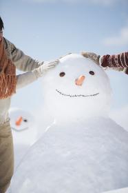 雪だるまを作るカップルの手元