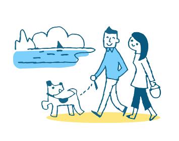 海岸を犬と散歩をするカップル