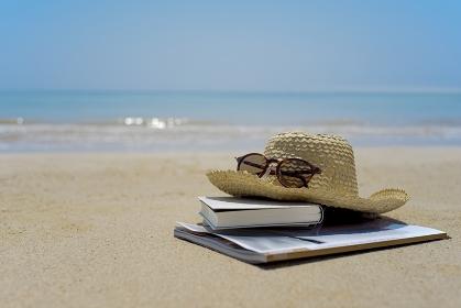 砂浜に置かれた本と麦わら帽子とサングラス