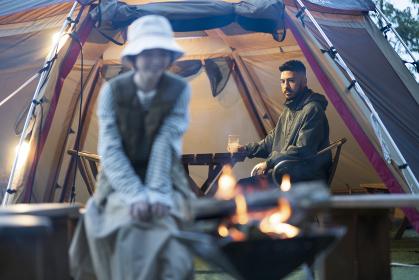 暗がりの中、焚き火を楽しむ男女