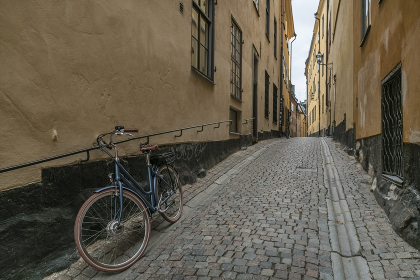 bike parked in medieval street with yellow houses and coble  stones