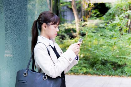 【東京都】屋外でスマホで通話するビジネスウーマン