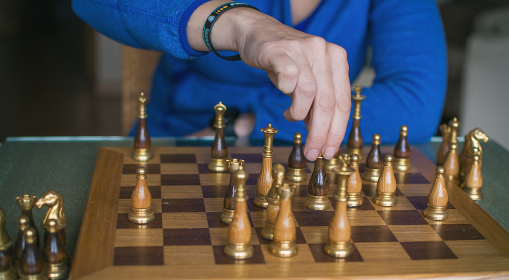 Unrecognizable Person Making A Chess Move With Strategy. Mental Sport