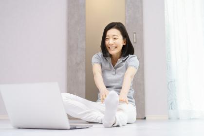 パソコンを見ながら軽い運動をする女性(40代、50代イメージ)