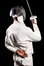 Rear view of man wearing fencing suit practicing with sword