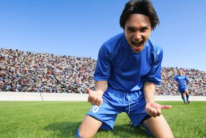 芝生の上で喜ぶサッカー選手