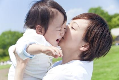 男の子を抱き上げキスをする母親