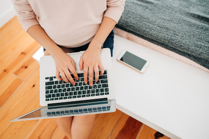 Unrecognisable woman typing on laptop while sitting, top view
