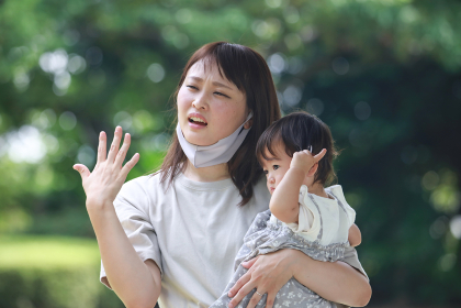 子供を抱っこし暑そうな母親