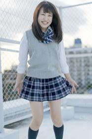 学校の屋上でほほ笑む女子高生