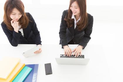 パソコンとタブレットを見る二人の女性 ビジネス