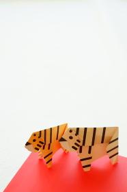 年賀状に使える白い背景に折り紙の左を向いた2頭の黄色い虎とホワイトタイガー縦構図