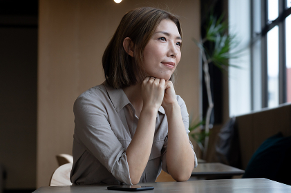 Pensive asian woman looking out of window in office cafeteria. social distancing in business office workplace during covid 19 coronavirus pandemic.