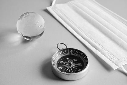 灰色の紙の上に置いた不織布マスクと方位磁石とガラスの地球。モノクローム。